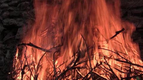 Big pile of dry twigs burning. A big fire red. Fire burns near a stone wall old. Footage