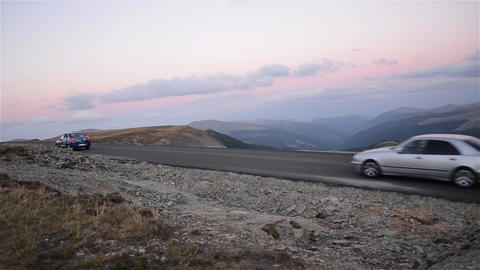 More cars go on a paved road, located high in the mountains, in a beautiful and  Footage
