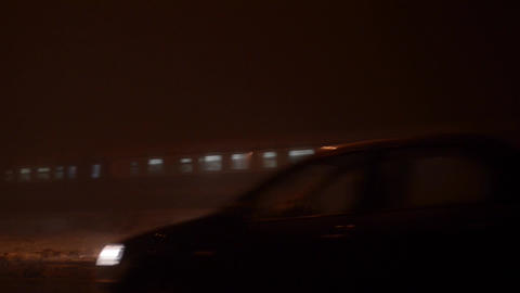 Night train rids through dense fog on the outskirts of town, beside a busy road  Footage