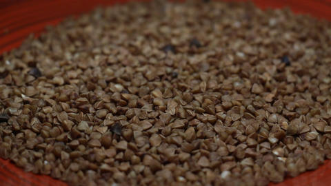 Handful of Buckwheat on a Red Plate Close Up Rotating Live Action