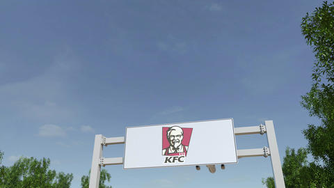 Airplane flying over advertising billboard with Kentucky Fried Chicken KFC logo Footage