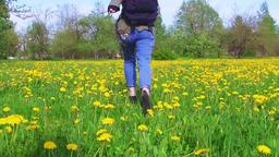 Girl hiker running on beautiful field of dandelion flowers Footage
