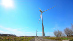 Wind turbine generating electricity on blue sky. Low angle view Footage