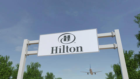 Airplane flying over advertising billboard with Hilton... Stock Video Footage