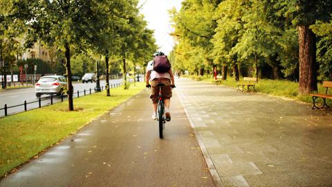Unknown man cycling along urban bike path after summer rain Footage
