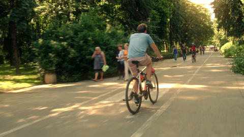 WARSAW, POLAND - JULY 11, 2017. People cycling and walking along the city park Footage