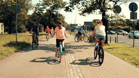 WARSAW, POLAND - JULY 11, 2017. People cycling along the city street sidewalk Footage