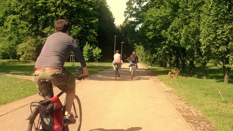 Unknown people cycling along summer park road Footage