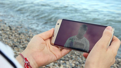 Girl Watching YouTube on Her Smartphone on the Beach Filmmaterial