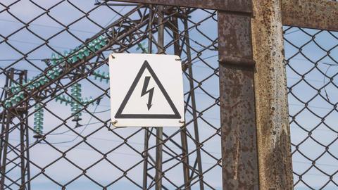 Electric high-voltage substation beyond the fence. Hazard warning sign. Danger Footage