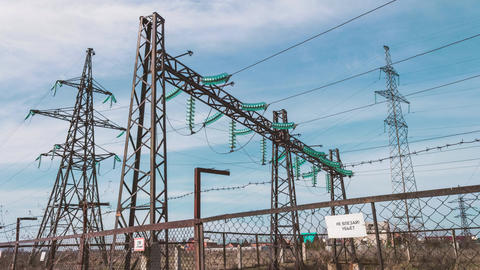 High-voltage electrical substation. Pylons with insulators and wires behind a Footage
