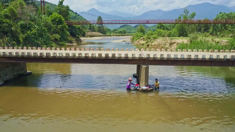 Drone View Women Washes Clothes in River against Nature Footage