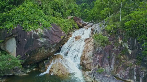 Flycam Approaches Waterfall Cascade Flowing across Boulders Footage