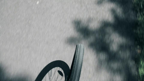 Blurred asphalt road chalk drawing and spinning bike front wheel Footage