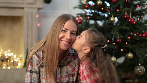 Little girl kissing her mother at Christmas Footage