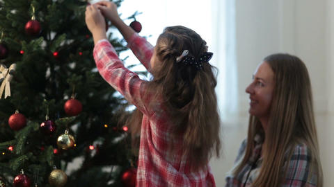 Girl helping her mom to decorate family xmas tree Footage