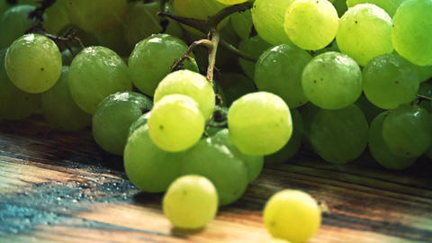 Spraying water over ripe fresh green grapes on a wooden table Footage
