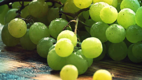 Spraying water over ripe fresh green grapes on a wooden... Stock Video Footage