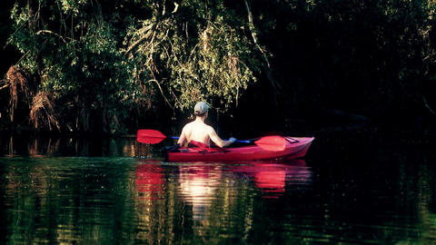 Unknown man in red kayak floating down the river and observing forest riverbanks Footage