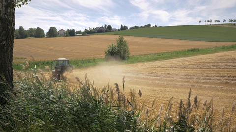 Tractor plowing wheat field and turning around Archivo