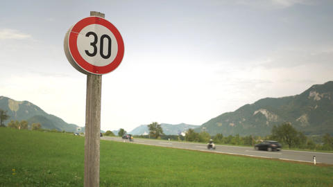 Speed limit 30kmph sign with a highway and mountains view Archivo