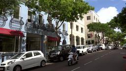 Bermuda capital city Hamilton scooters drive downhill on Reid Street Footage