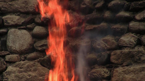 Old wall of stone, found in woods and beside him a consuming fire. Fire at first Live Action