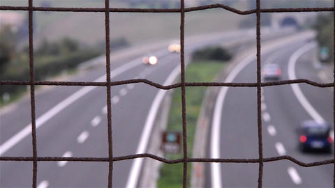 Vehicle traffic on the highway, seen through mesh fence placed on a bridge locat Footage