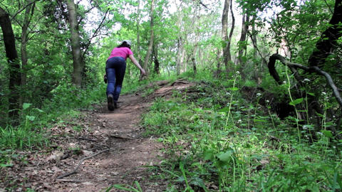 Young girl walking alone on a trail in a deciduous forest 5 Footage