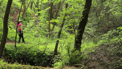 Young girl walking alone on a trail in a deciduous forest. A walk throug the for Live Action