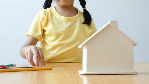 Asian little girl putting money coin into clear house bank metaphor saving money Footage