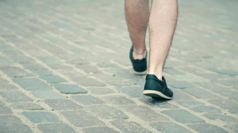 Adult man wearing shorts walks on cobblestone pavement Footage