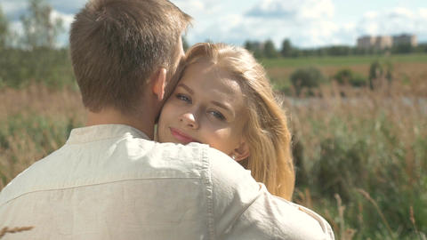 Portrait of a blonde girl who is hugging her boyfriend and smiling happily Footage