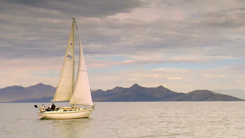 A sailboat glides on calm water near mountains Archivo