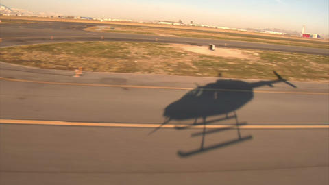 Shadow of helicopter hovering over airport runway Footage
