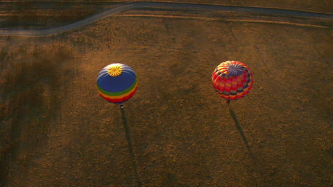 Two hot air balloons with long shadows shot from above Footage