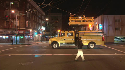 Workers inspect overhead wires in san francisco at night time Live Action