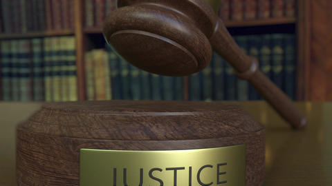 Judge's gavel falling and hitting the block with JUSTICE inscription Footage