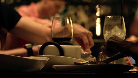 Unknown people eating steaks in a restaurant, table close-up shot Footage