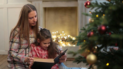 Mother reading book to daughter near xmas tree Archivo
