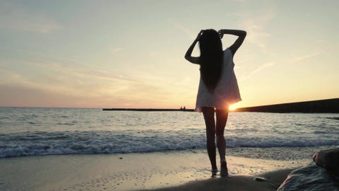 beautiful girl enjoys life in the rays of the sunset light on the beach Archivo