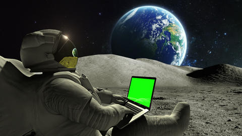 Astronaut using laptop on the moon green screen Live Action