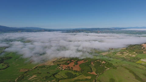 Fog over farmland hill country in Tuscany, aerial Footage