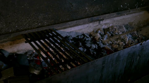 Cook stirs the coals with a metal stick Footage