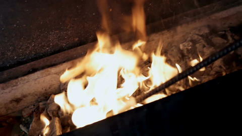 Man stirs coals in a brazier with a metal stick Footage