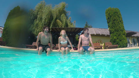 Three friends smiling relaxed enter the pool and start swimming Footage