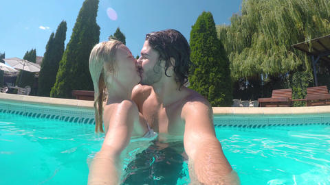 Couple taking video shots in the water while they are kissing and hugging Footage