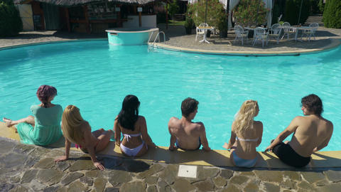 Group of friends sitting by the pool at a private villa waiting for the party to Footage