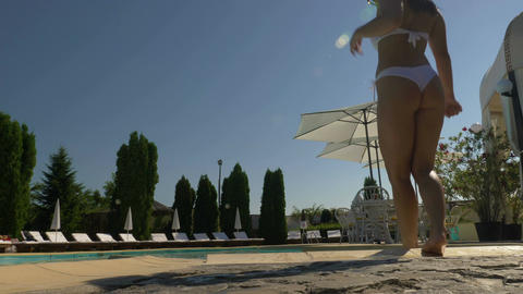 Sexy woman in white Brazilian swimsuit enters pool Footage