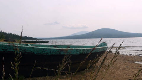 Rusty boat lies on the shore of the lake Footage